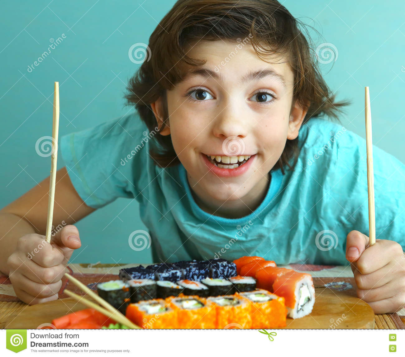 Menino considerável do Preteen com grupo do rolo de sushi