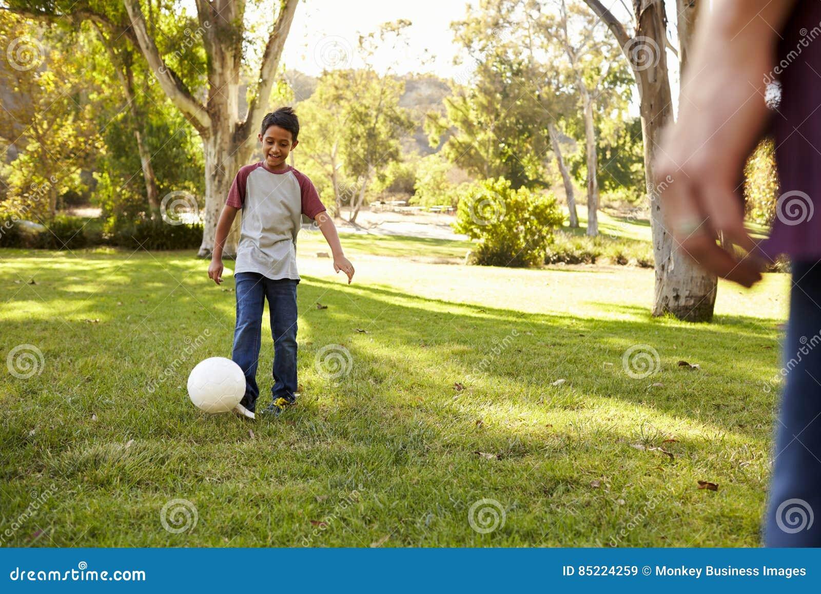 Menino da criança de sete anos que joga o futebol em um parque com paizinho