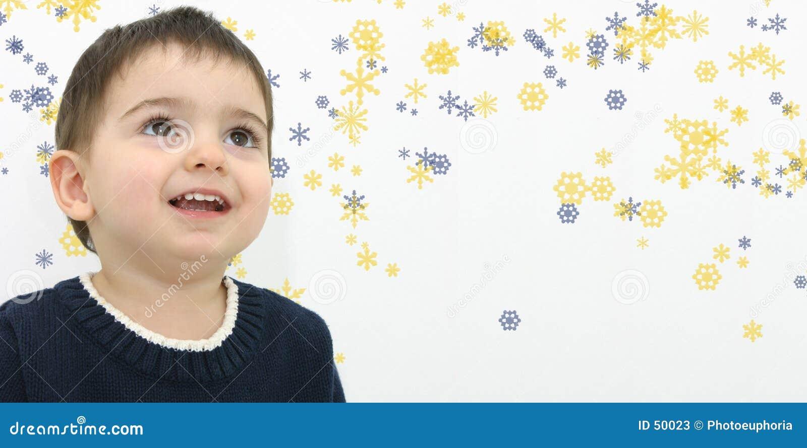 Menino da criança do inverno no fundo do floco de neve