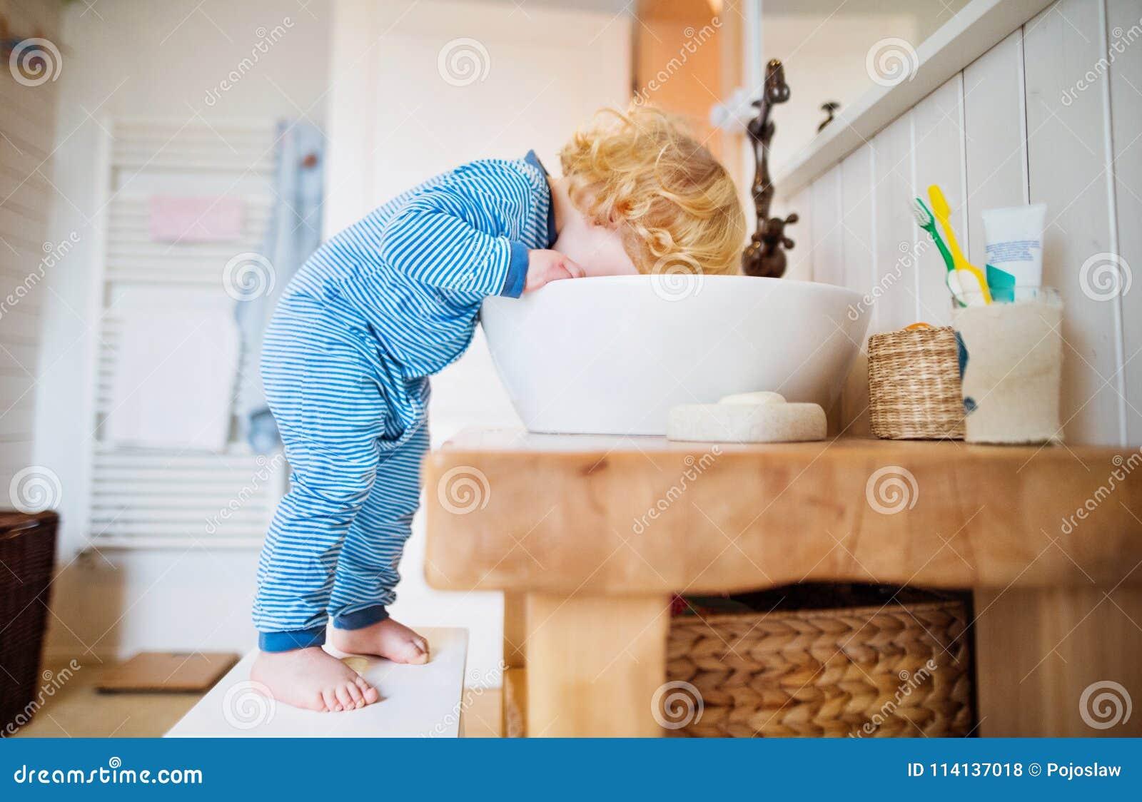Menino da criança em uma situação perigosa no banheiro