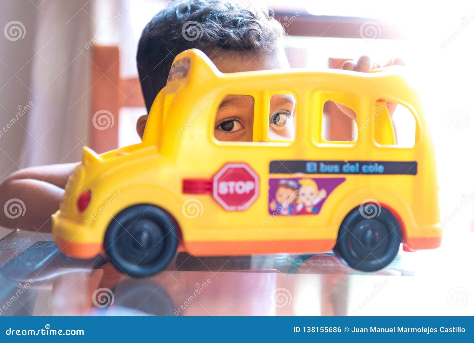 Menino da criança que joga com um brinquedo do ônibus escolar dentro