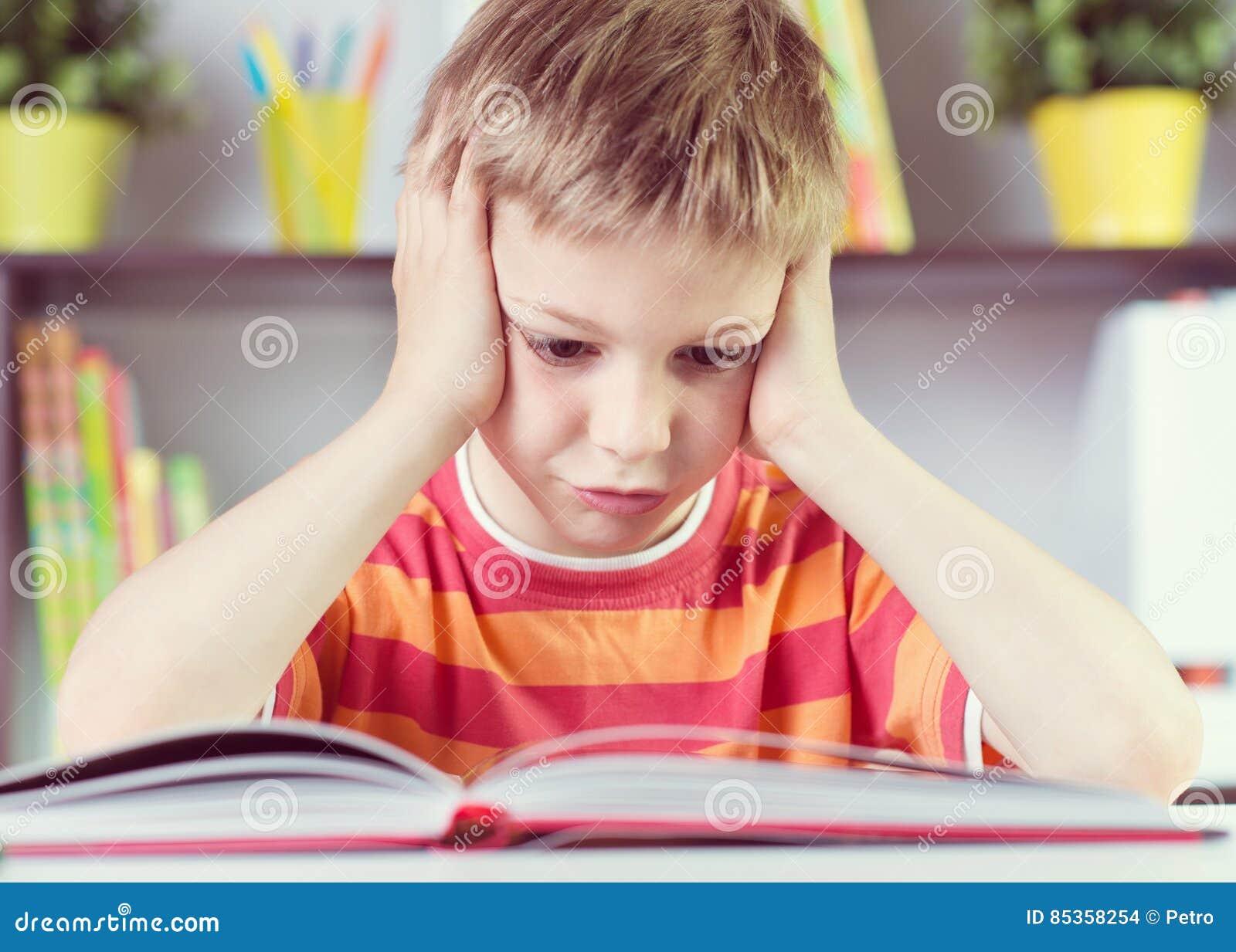 Menino da escola primária no boock da leitura da mesa