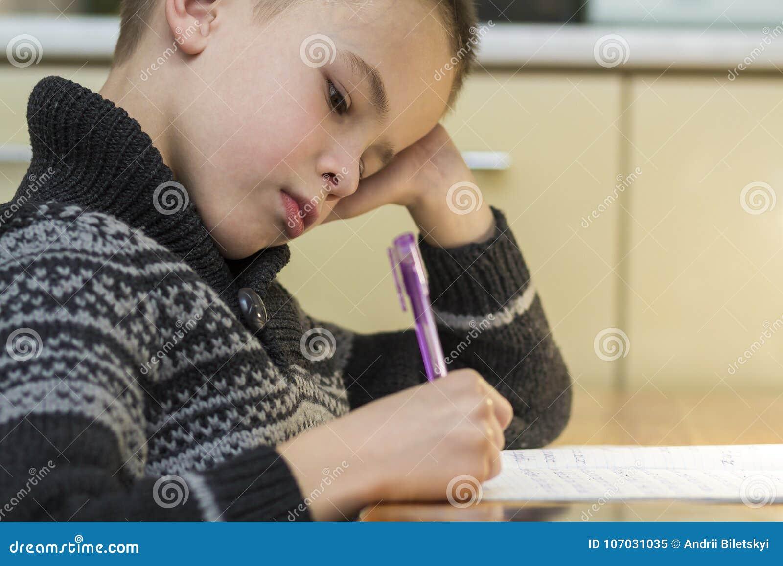 Menino da idade escolar da criança que faz seus trabalhos de casa