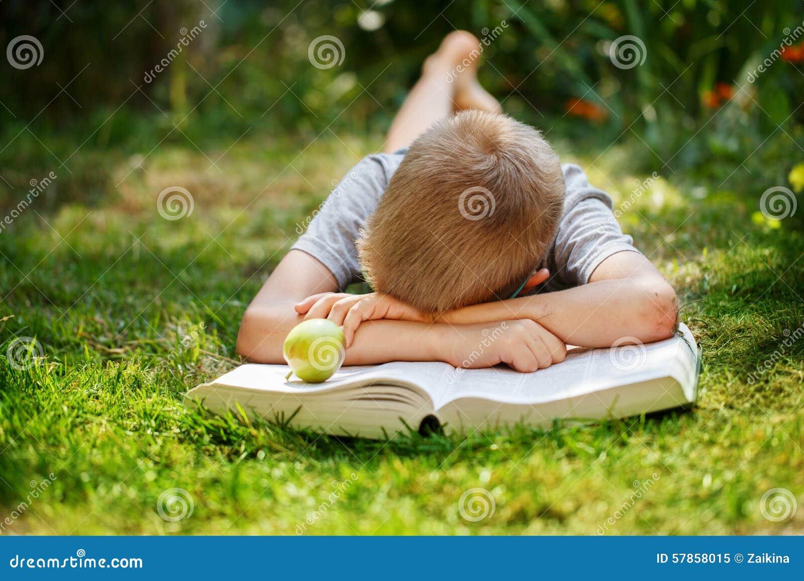 Menino de escola bonito que encontra-se em uma grama verde que não queira ler o livro menino que dorme perto dos livros