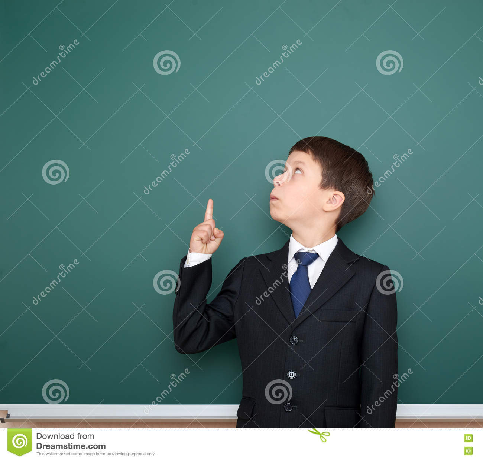 Menino de escola no dedo preto da mostra do terno acima do gesto e da maravilha, ponto no fundo verde do quadro, conceito da educ