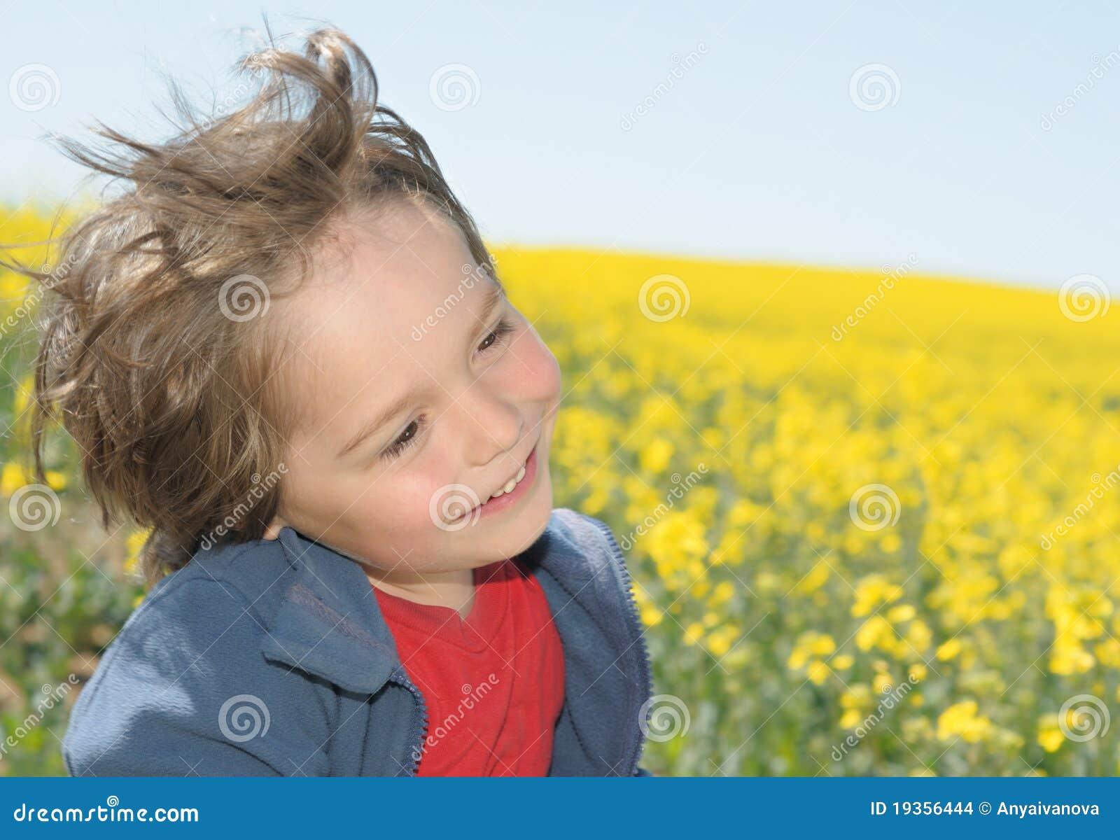 Menino de riso em um campo do rapeseed
