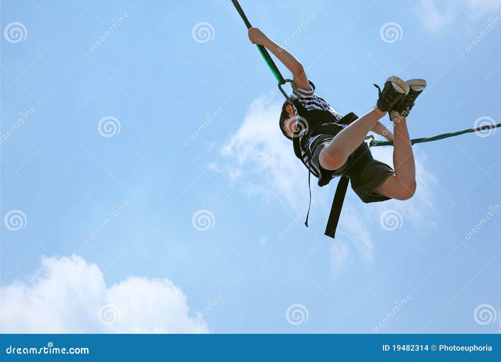 Menino de salto do tirante com mola de encontro ao céu com trajeto de grampeamento