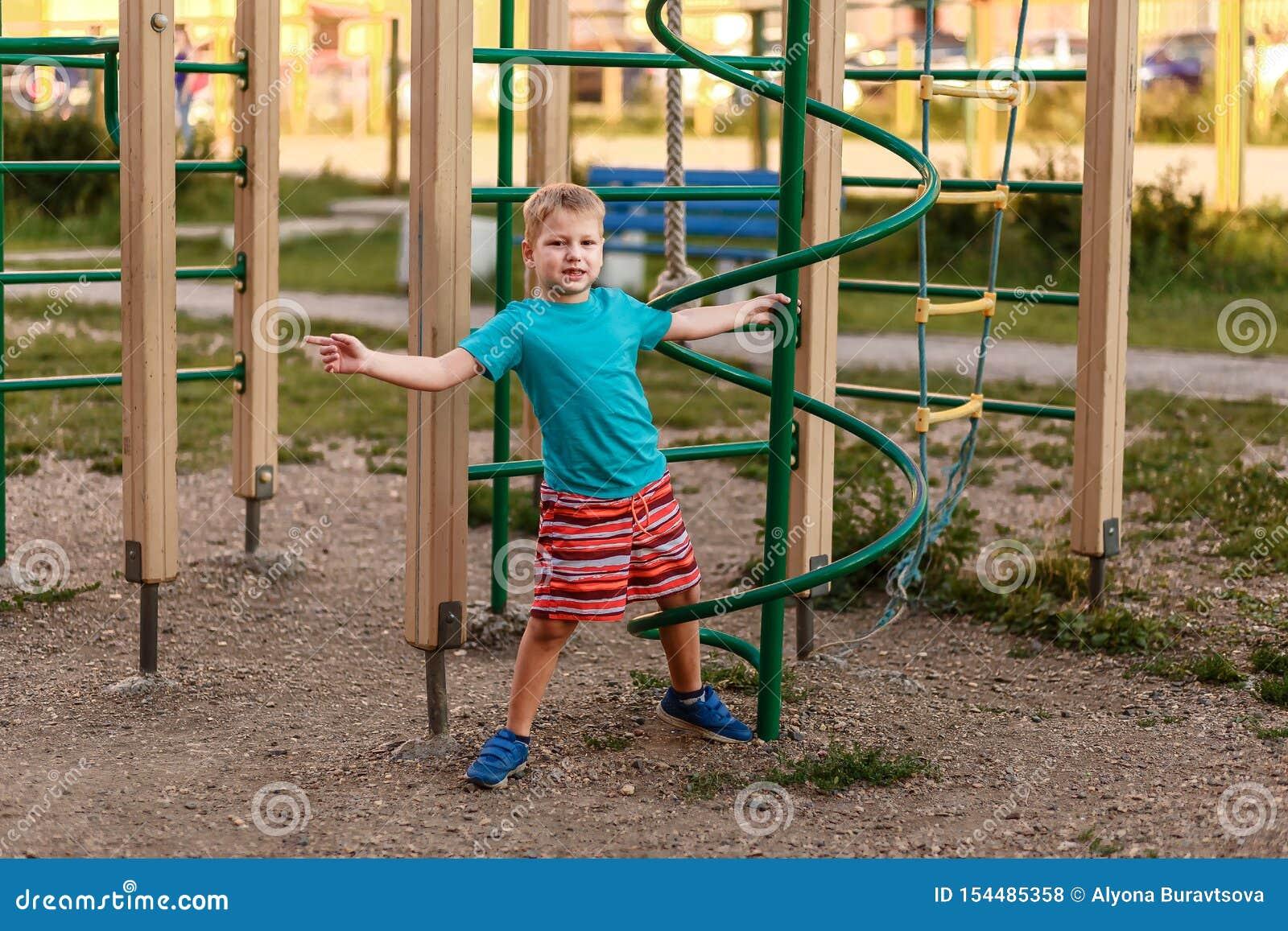 Menino de sete anos no short que joga no verão no campo de jogos