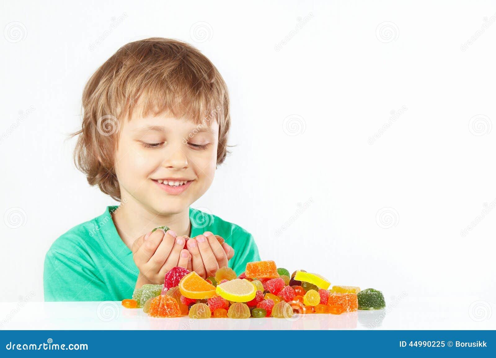 Menino de sorriso com doces e os doces coloridos da geleia no fundo branco