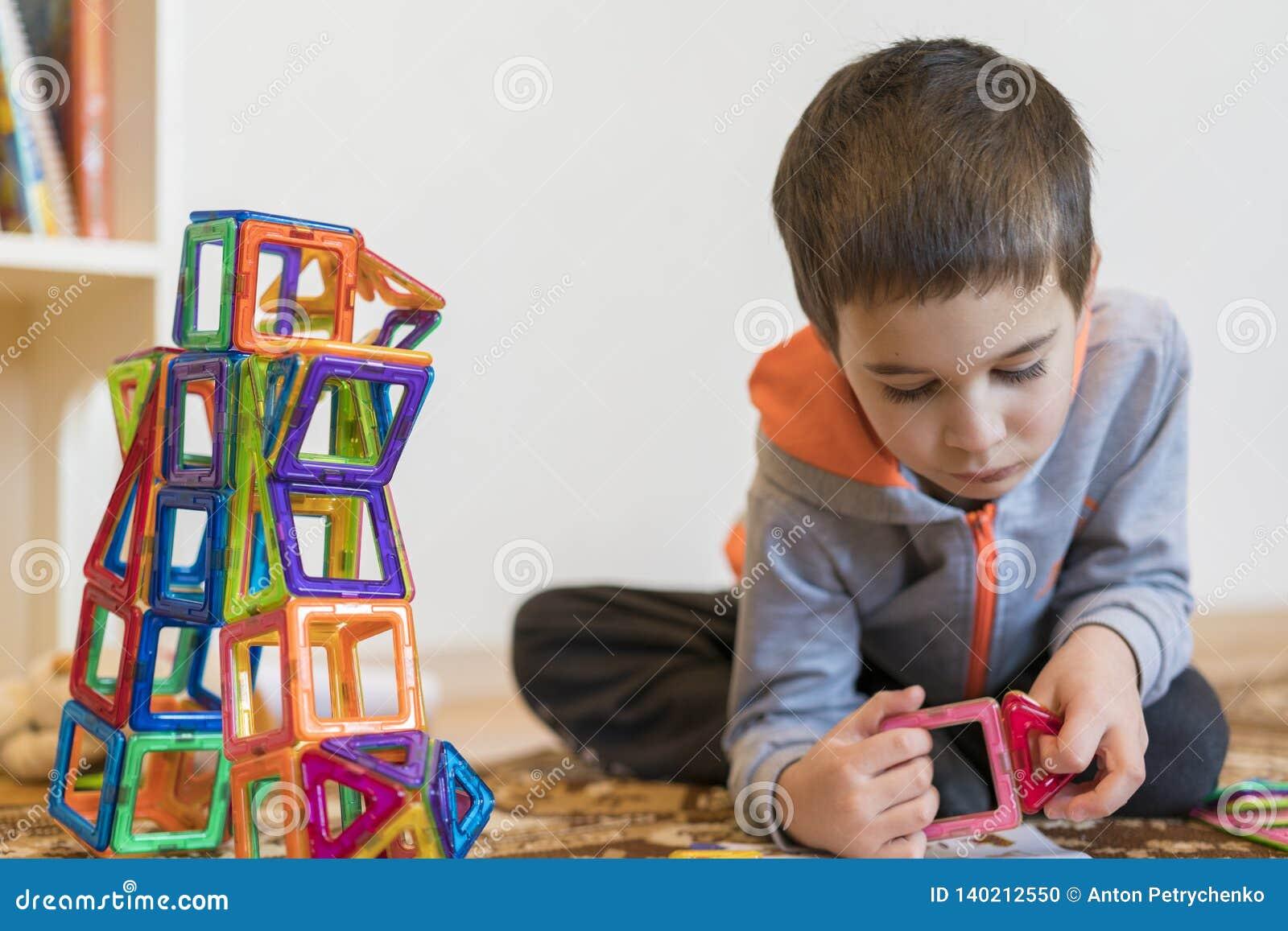 Menino de sorriso pequeno que joga com o brinquedo magnético do construtor Menino que joga brinquedos intelectuais