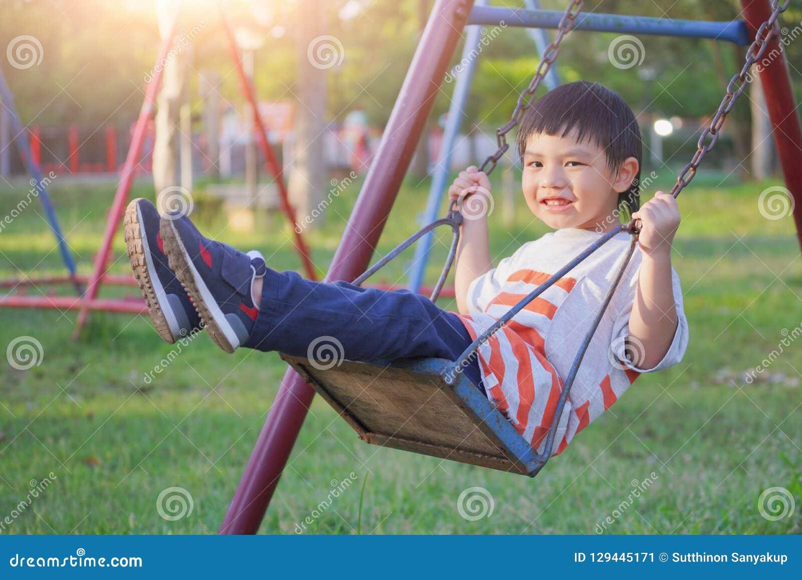 Menino de sorriso que balança em uma corda em um campo de jogos