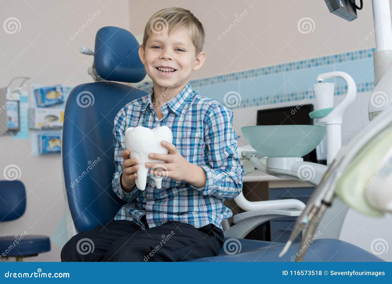 Menino de sorriso que guarda o modelo do dente em dentistas