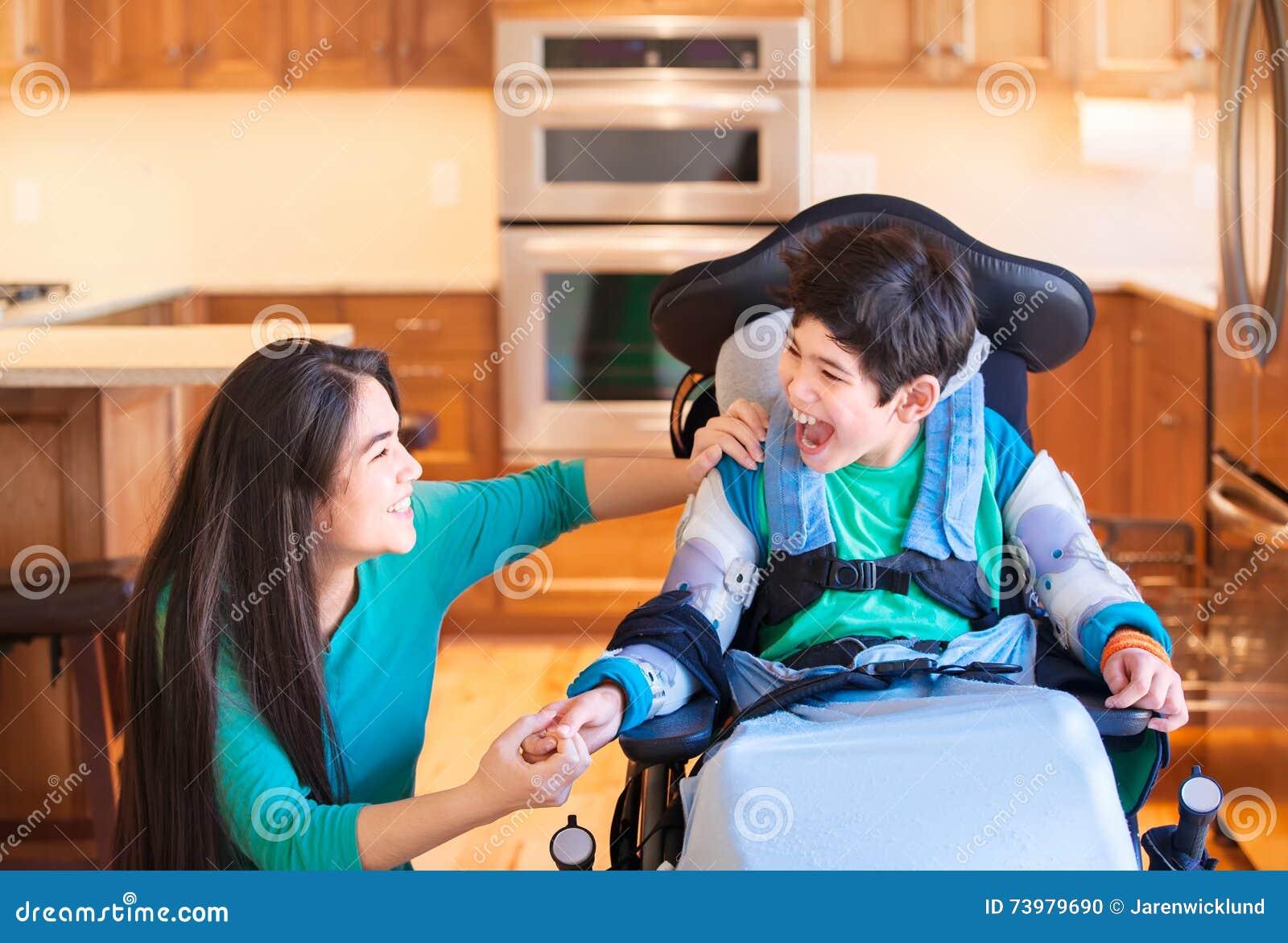 Menino deficiente na cadeira de rodas que ri com a irmã adolescente na cozinha