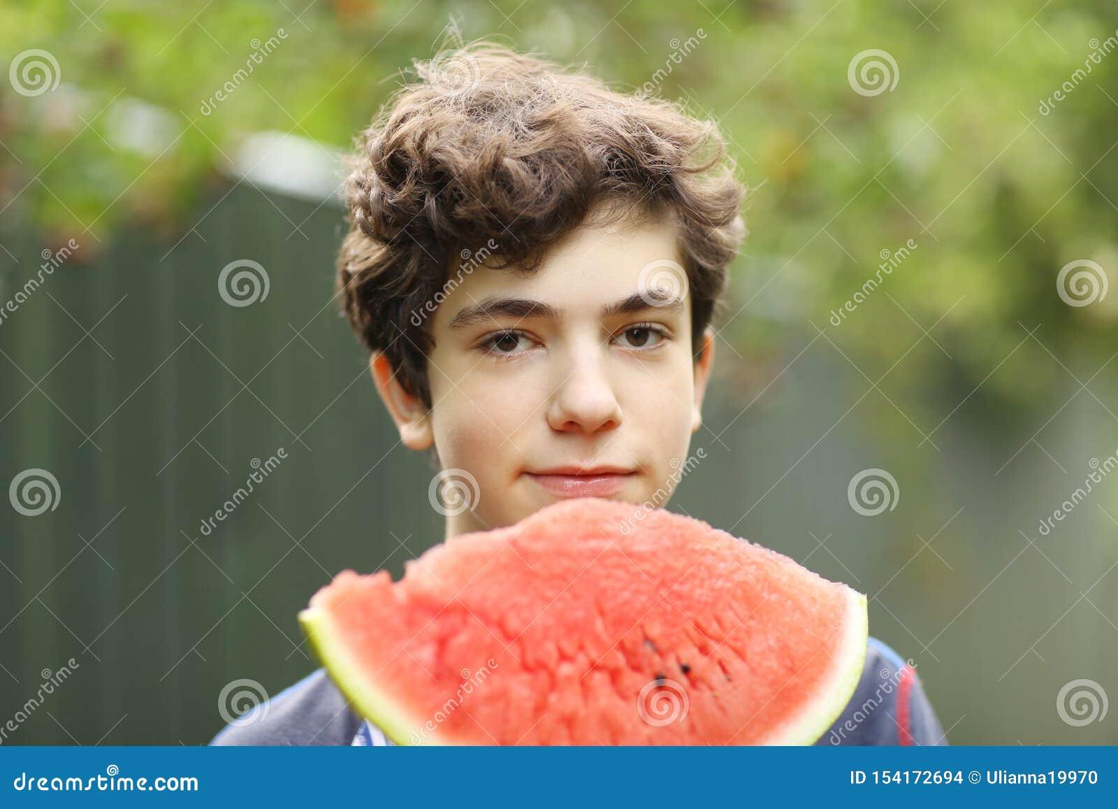 Menino do adolescente com fim cortado da melancia acima da foto