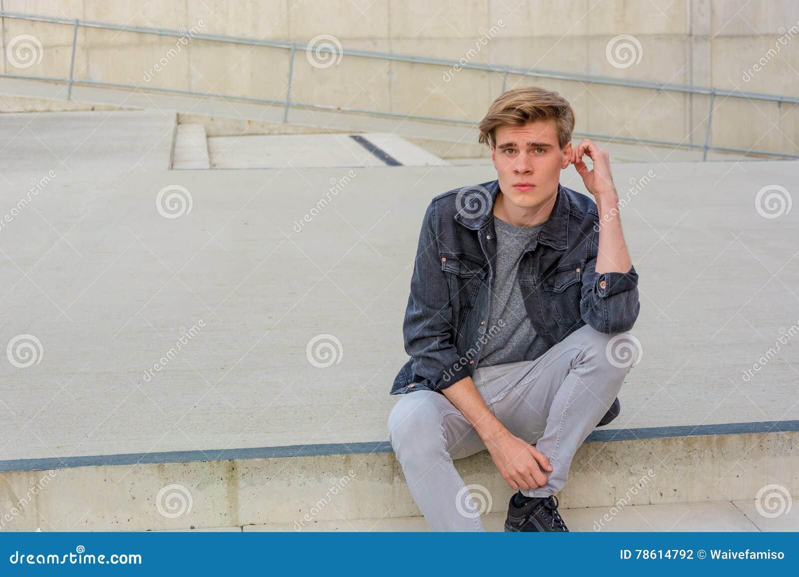Menino do adolescente que senta-se no pensamento das escadas