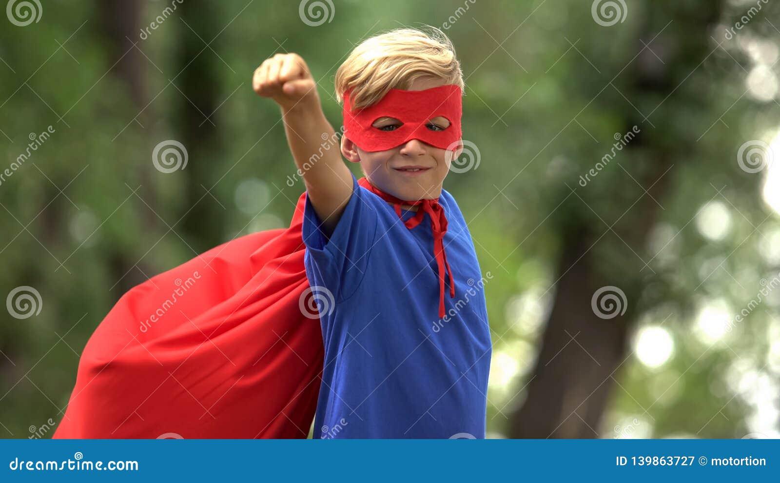 Menino do super-herói que joga no parque, fingindo voar, na criança corajoso e no conceito do vencedor