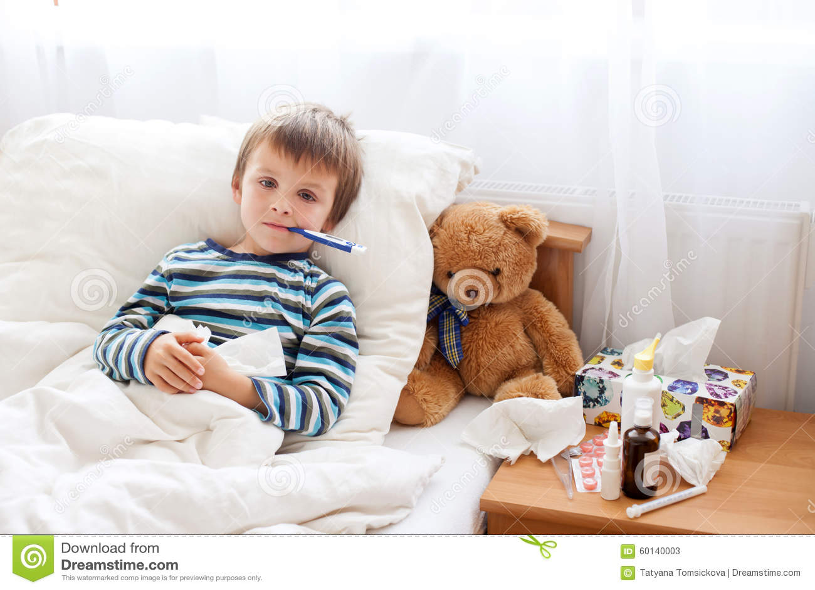 Menino doente da criança que encontra-se na cama com uma febre, descansando
