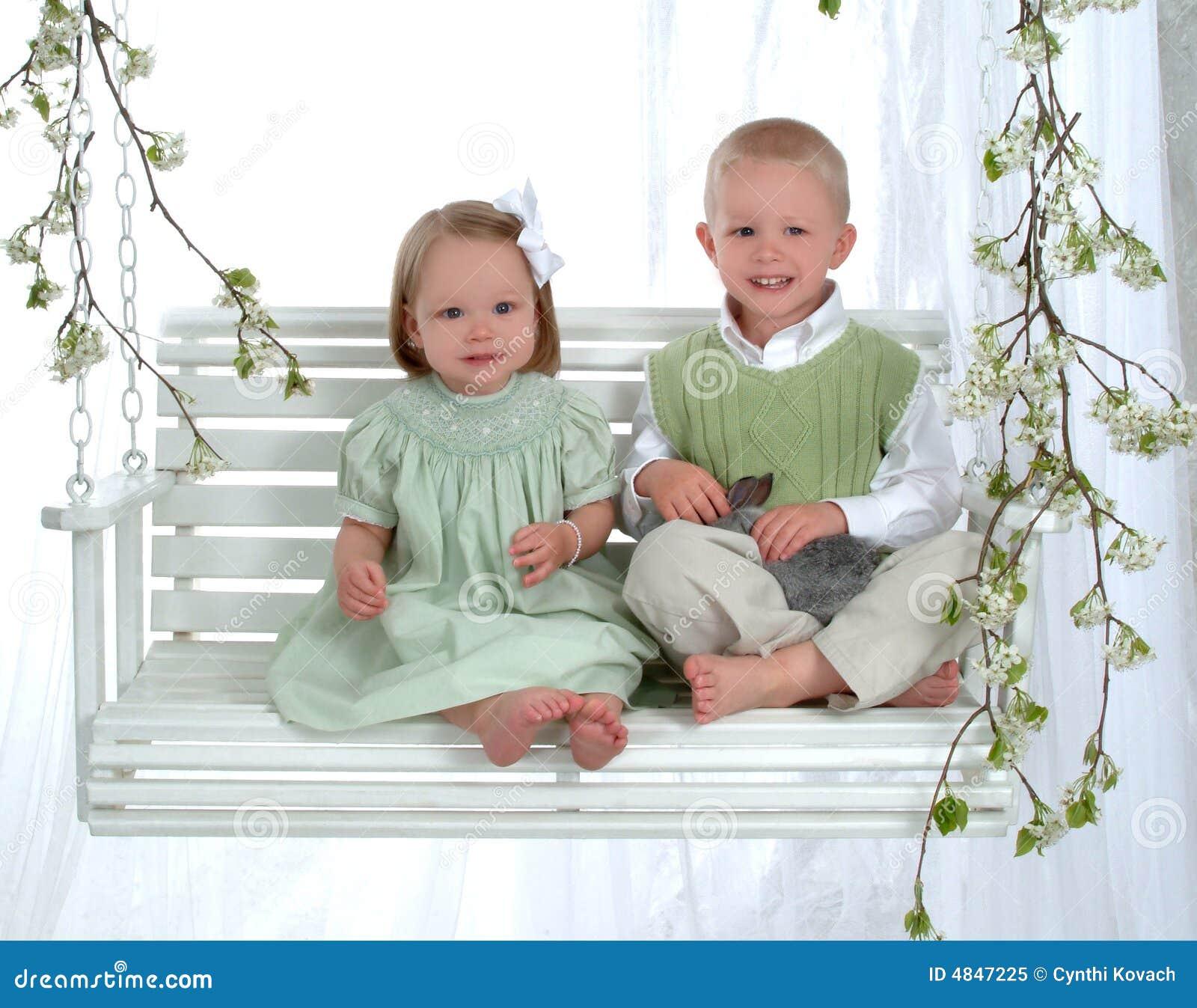 Menino e menina no balanço com coelho