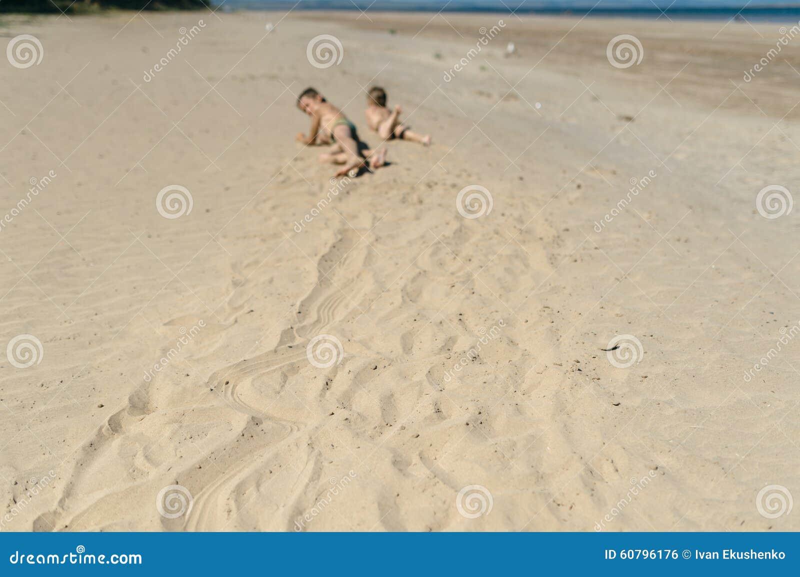 Menino e menina que rastejam na areia
