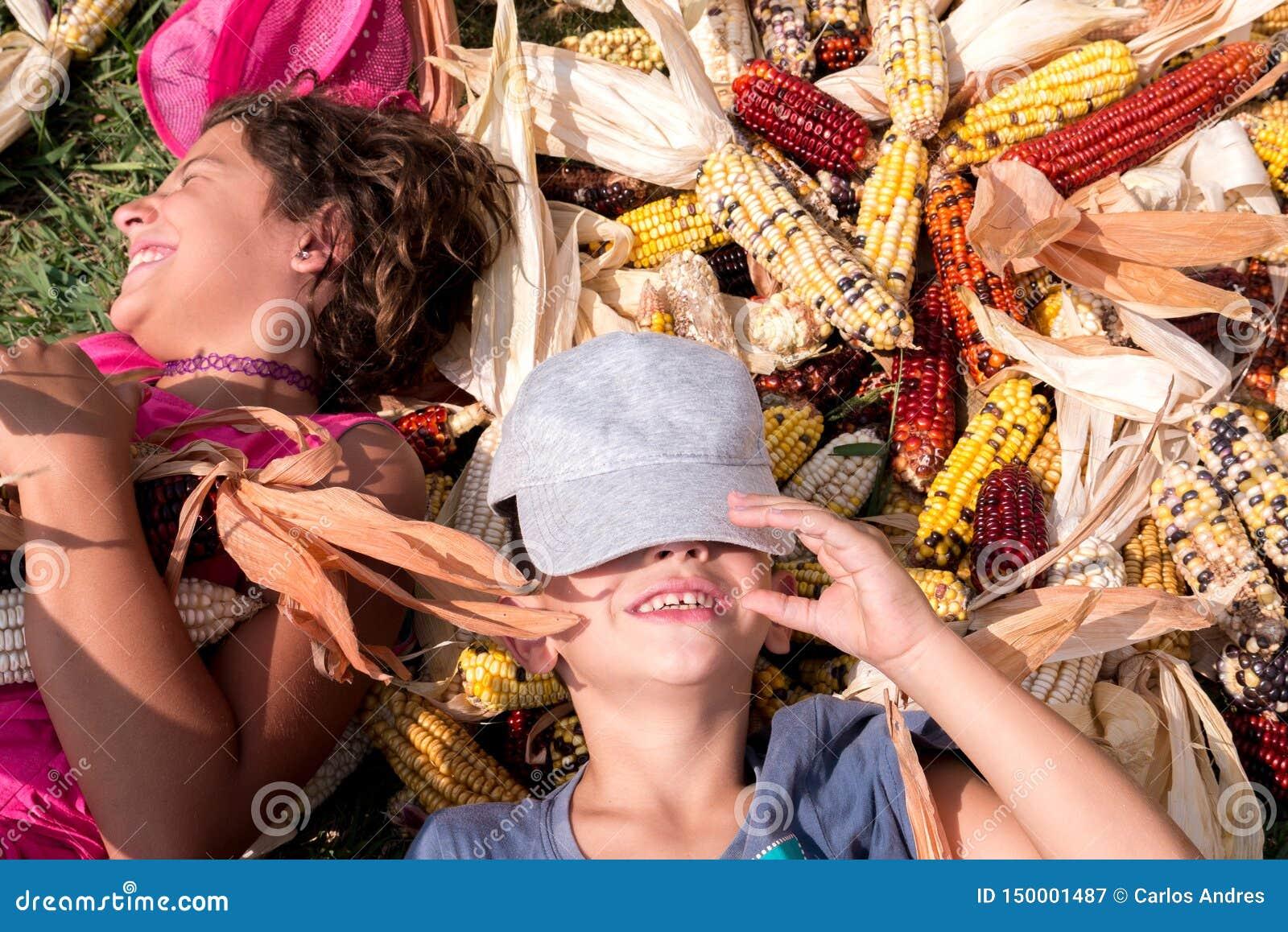 Menino e menina que têm o divertimento cercado por espigas de milho coloridas