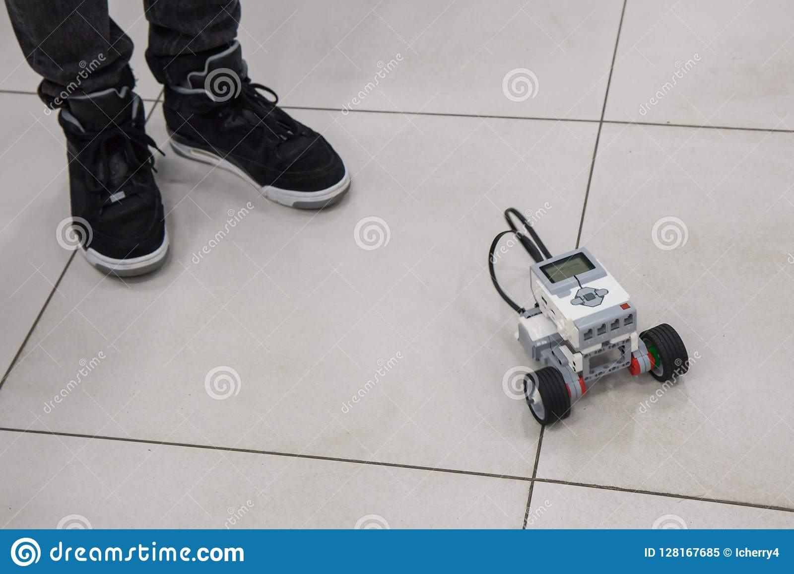 Menino e modelo montado do robô no laboratório da nanotecnologia