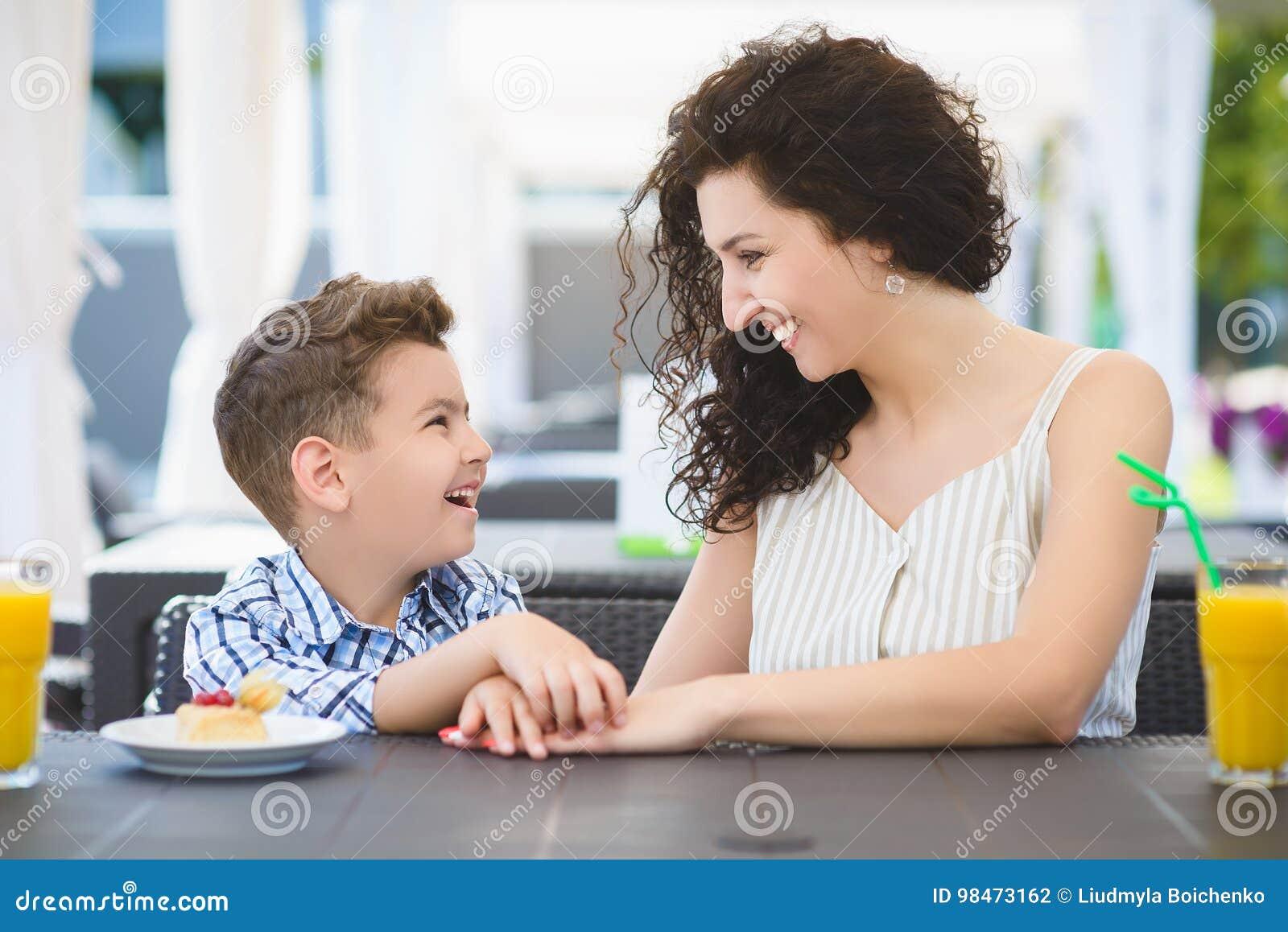 Menino e sua sobremesa do gosto da mãe com suco no restaurante do recurso exterior