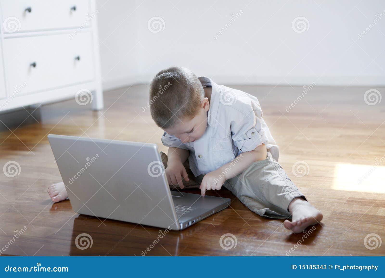 Menino em um portátil que senta-se para baixo no assoalho com os pés descalços