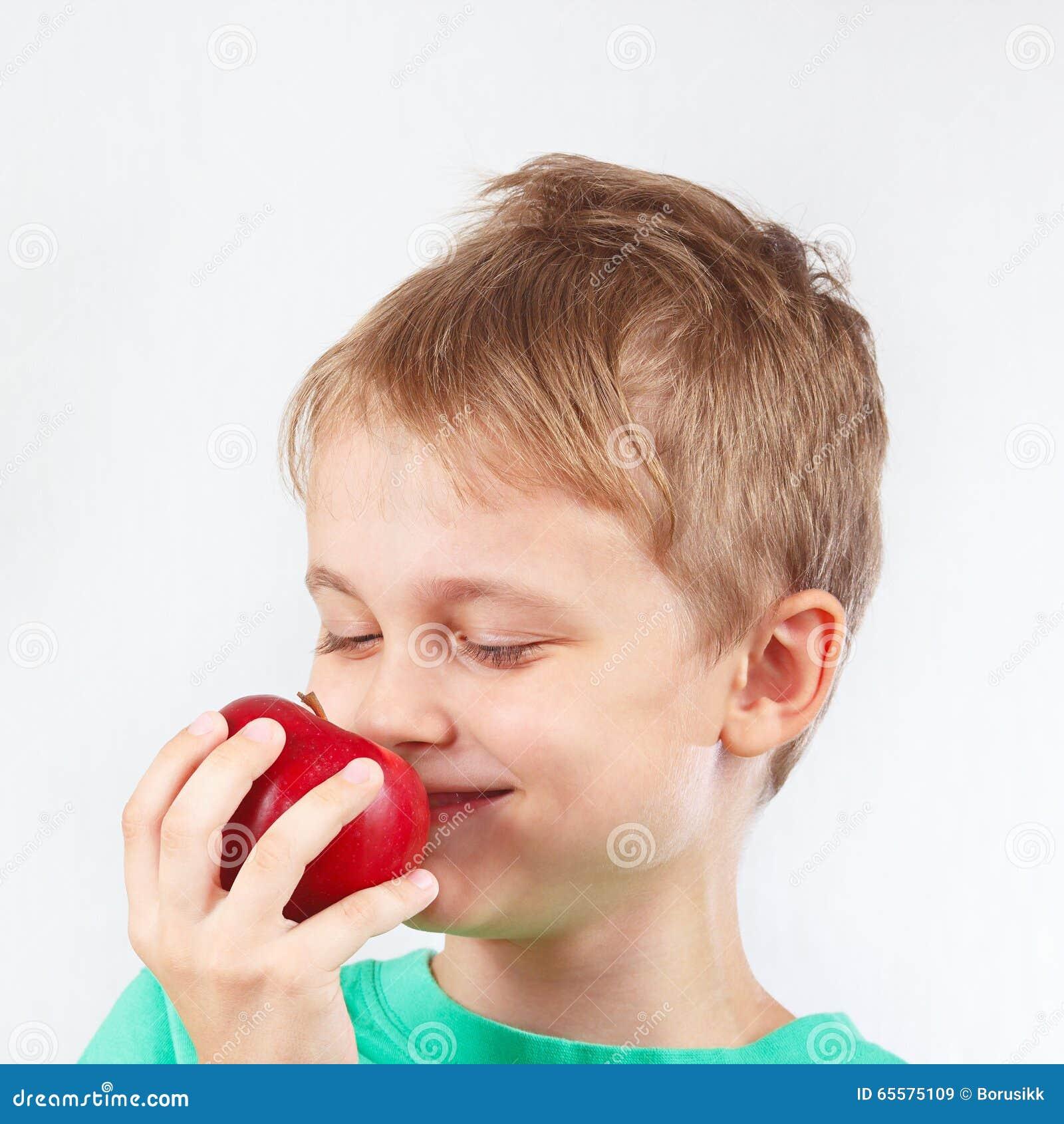 Menino engraçado pequeno na camisa verde com a maçã vermelha suculenta