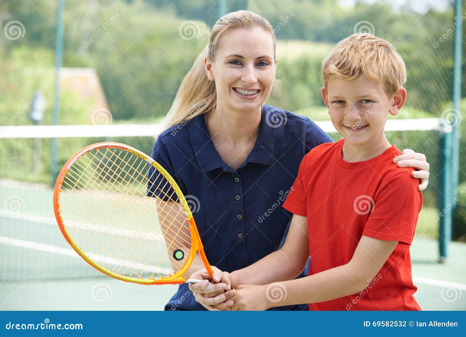 Menino fêmea de Giving Lesson To do treinador de tênis