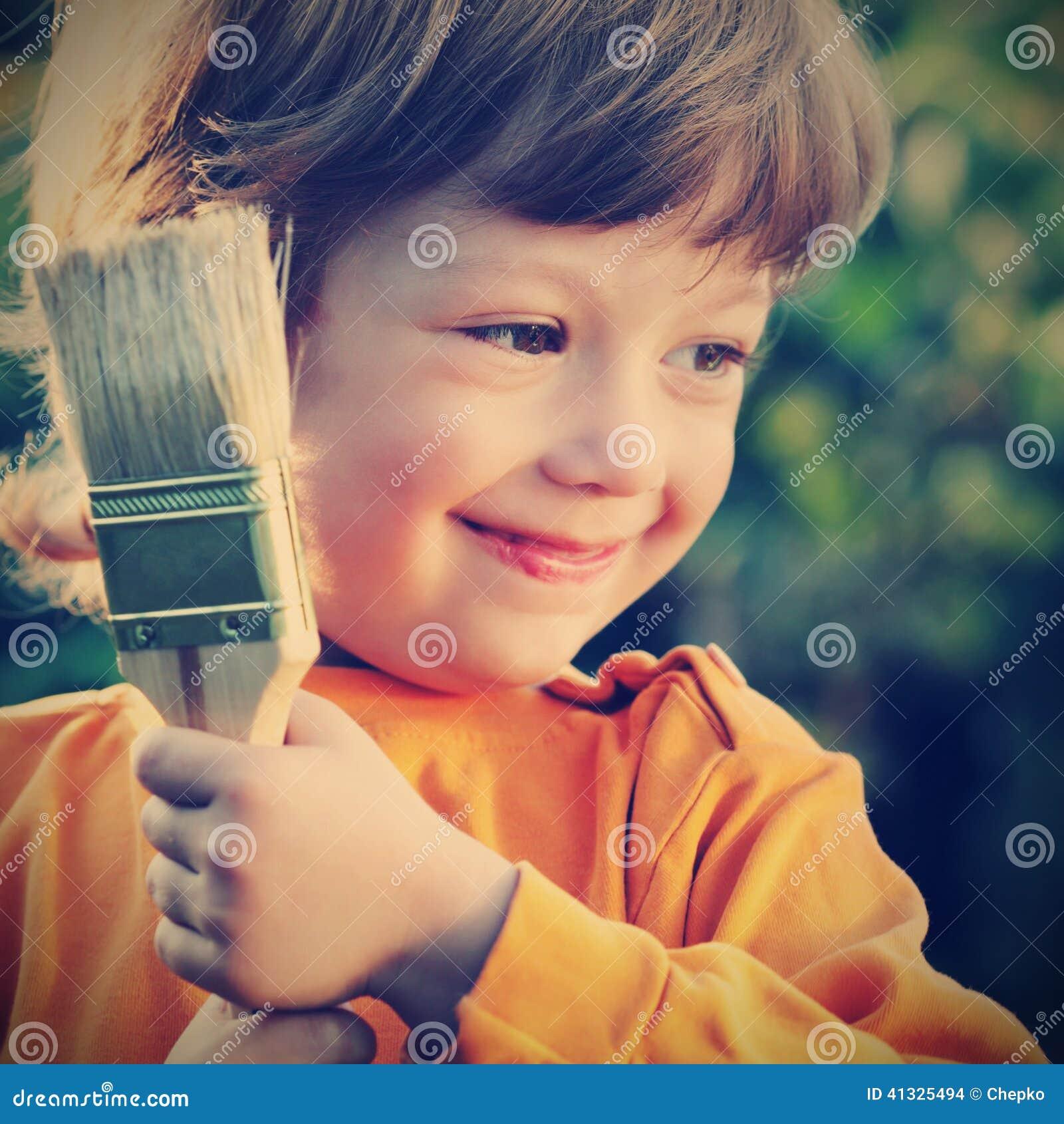 Menino feliz com escova de pintura