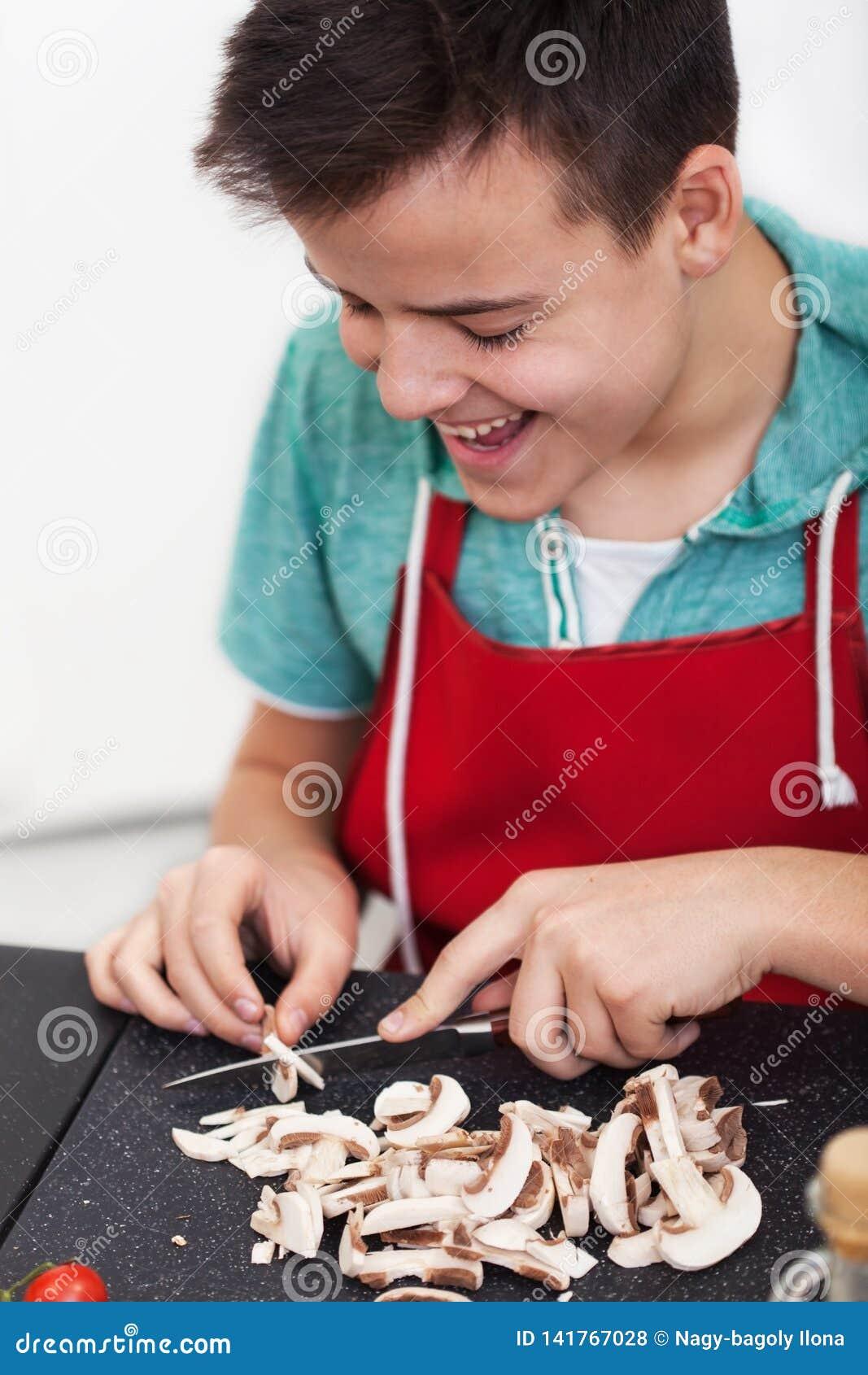 Menino feliz novo que prepara um prato na cozinha - cogumelos da fatia na placa de corte