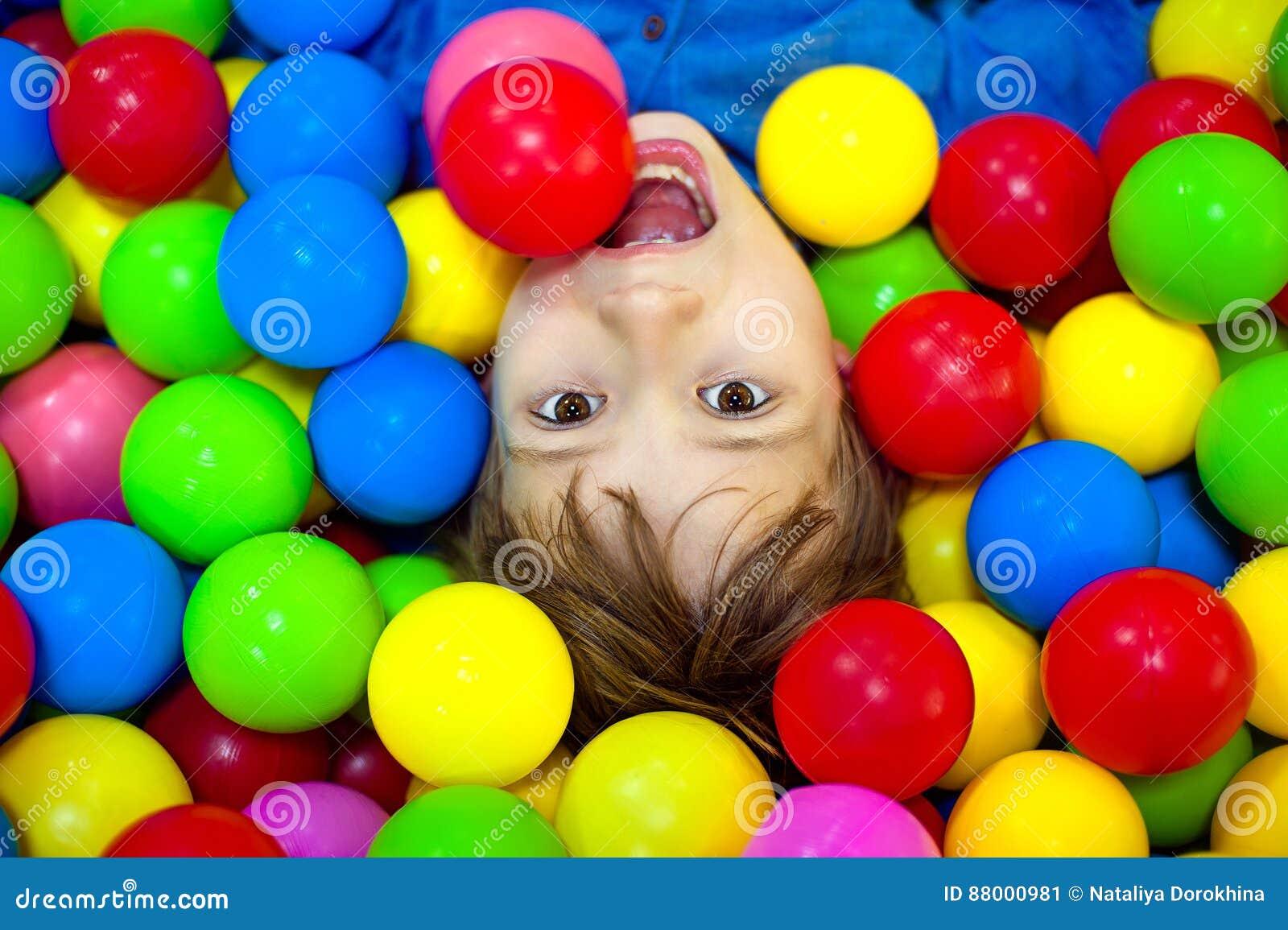 Menino feliz que joga em bolas coloridas Criança feliz que joga na opinião alta do campo de jogos plástico colorido das bolas
