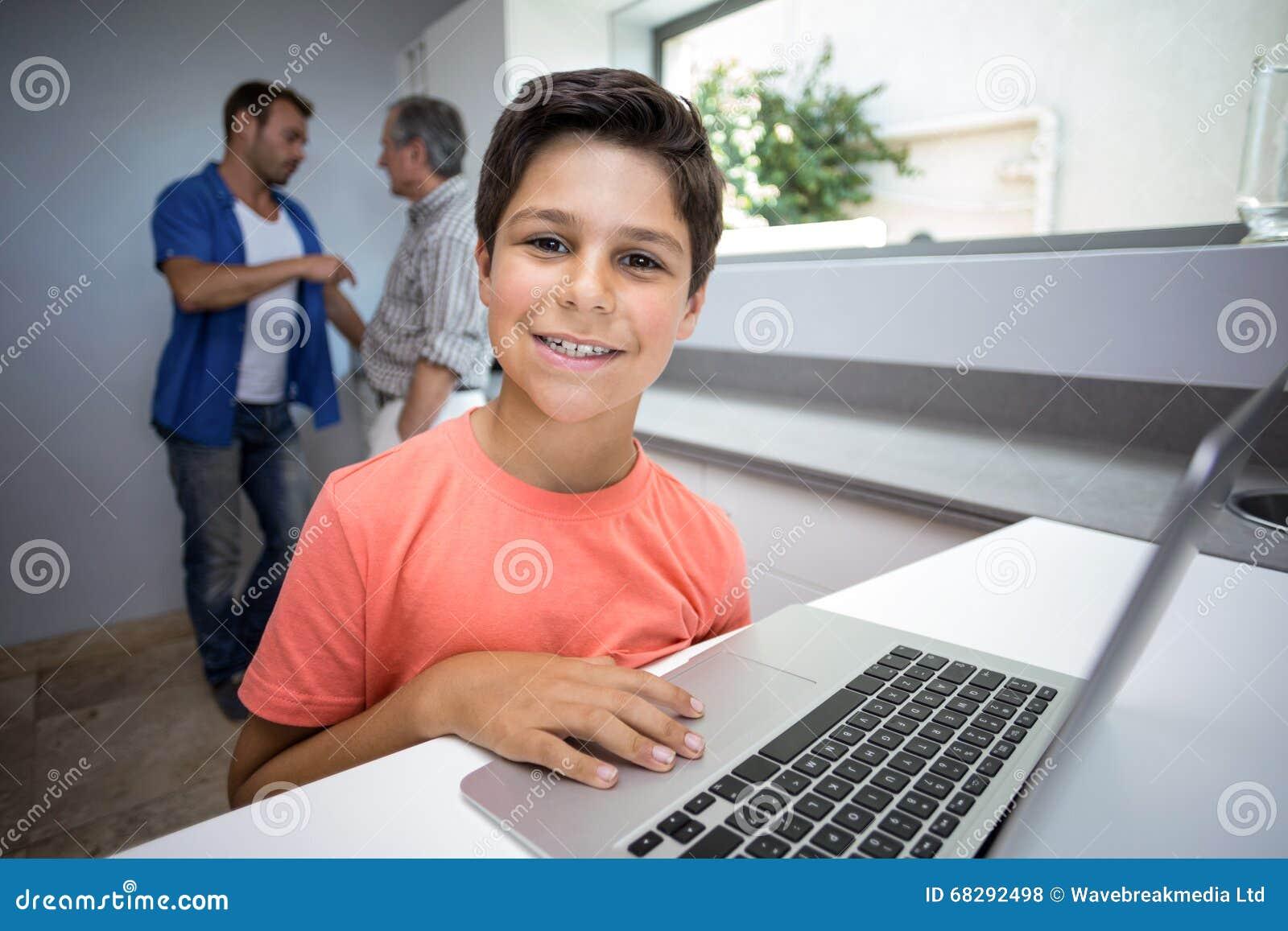 Menino feliz que usa o portátil