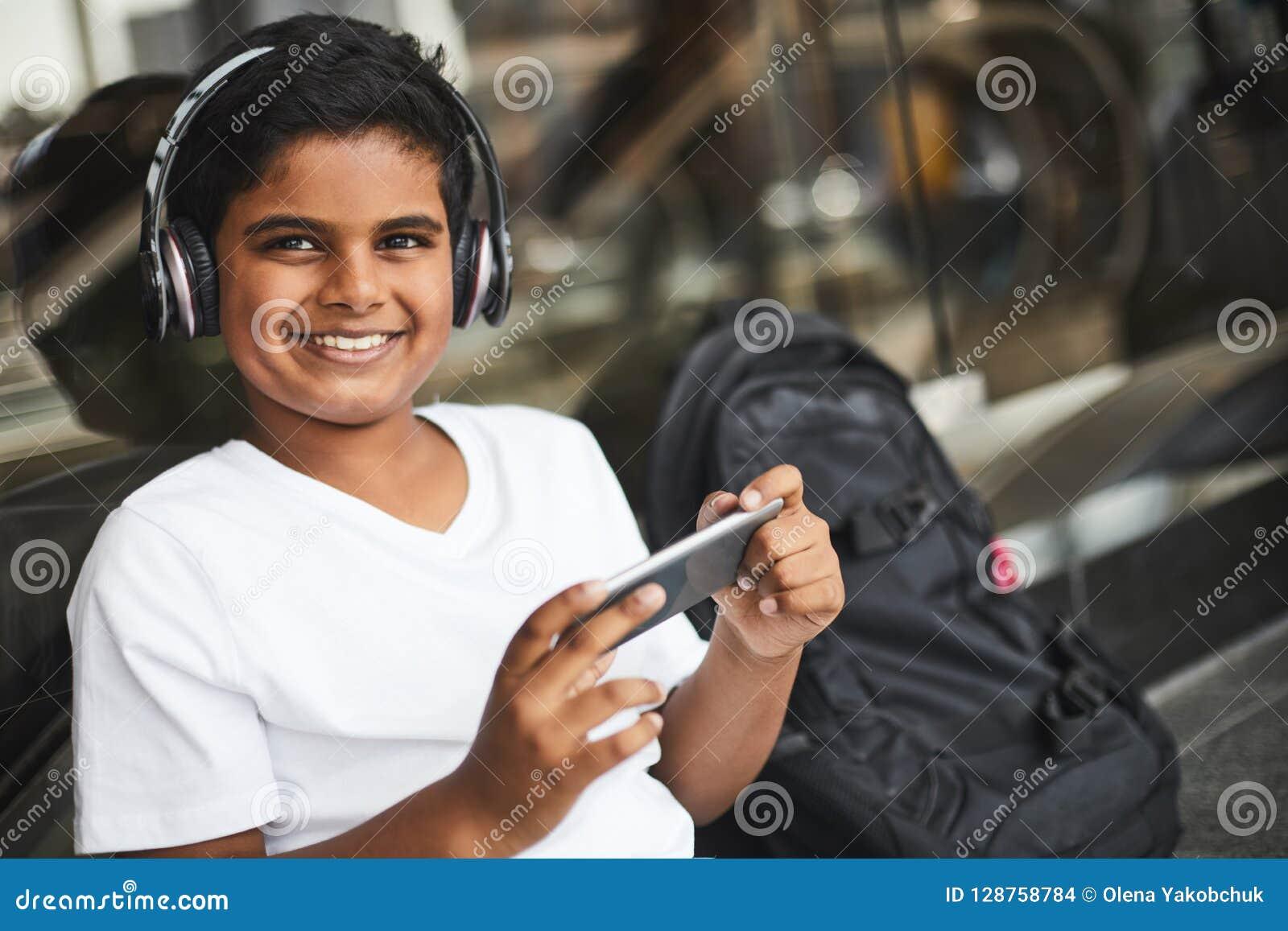 Menino hindu alegre que usa seus dispositivos espertos modernos