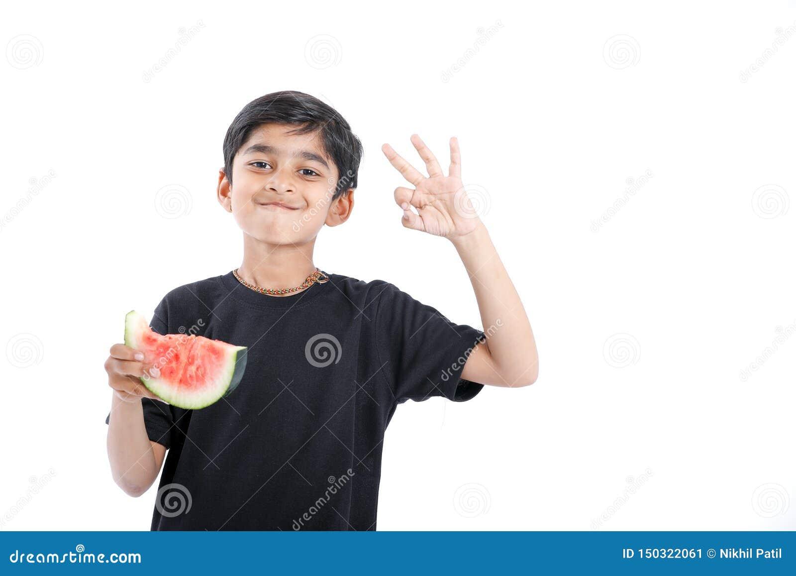 Menino indiano pequeno que come a melancia com expressões múltiplas