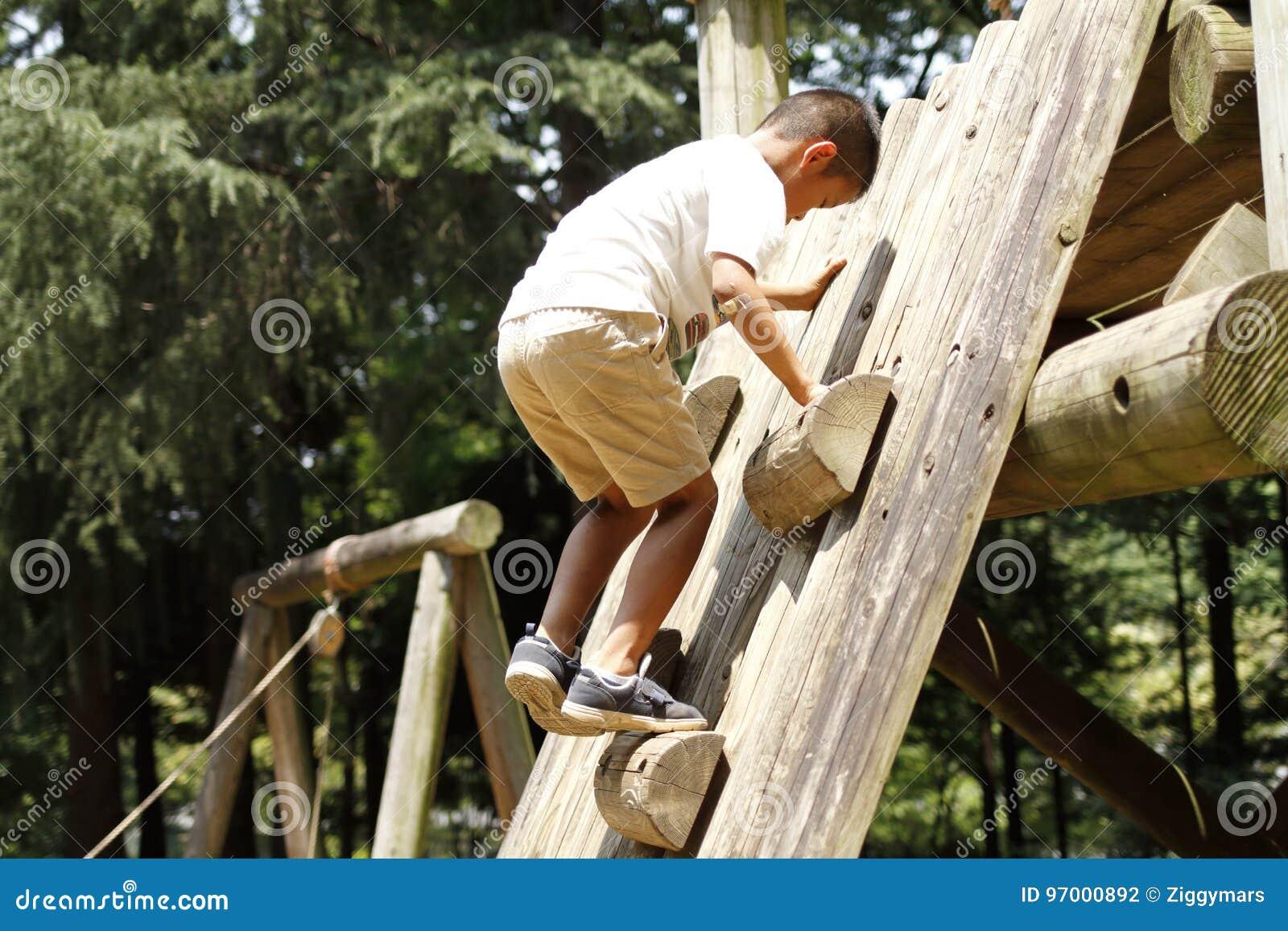 Menino japonês que escala na parede