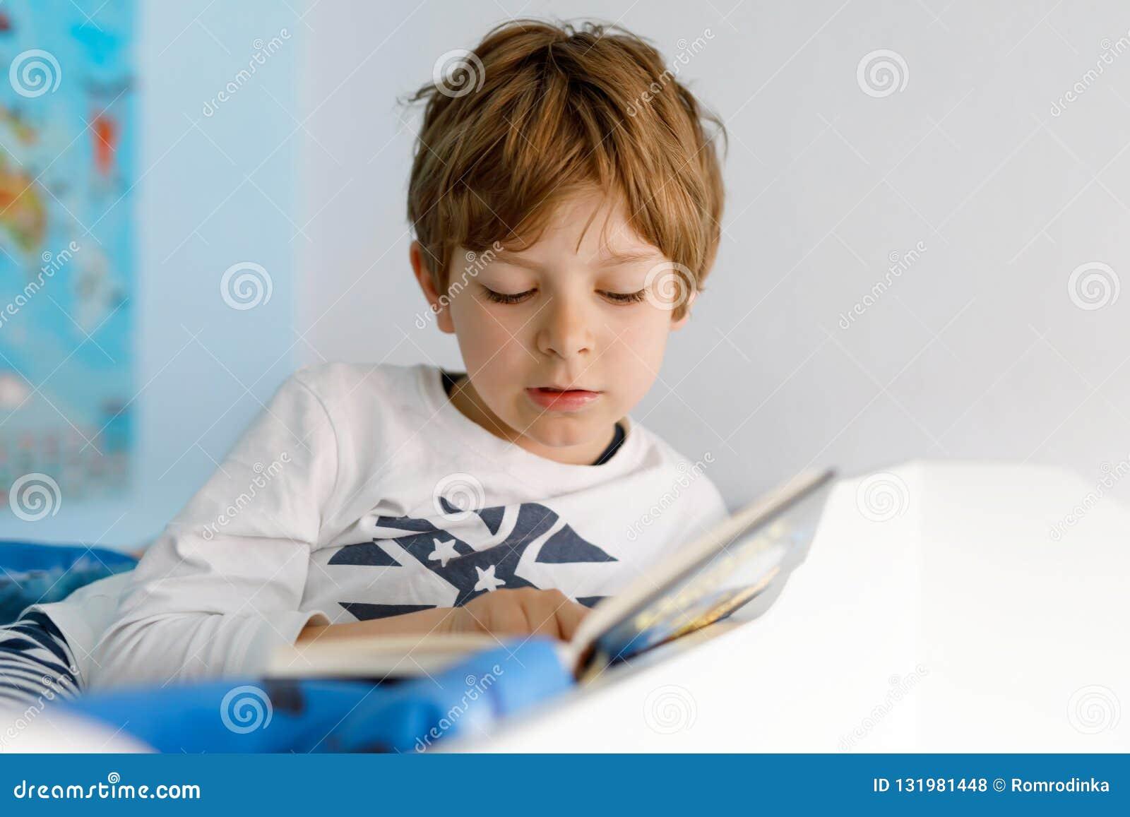 Menino louro bonito da criança no livro de leitura dos pijamas em seu quarto Criança entusiasmado que lê ruidosamente, sentando-s