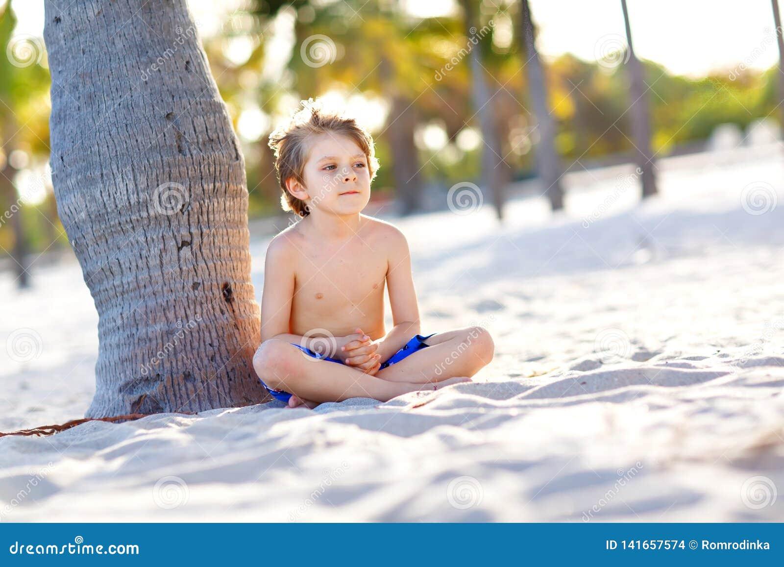 Menino louro da criança que tem o divertimento em Miami Beach, Key Biscayne Criança bonito saudável feliz que joga com areia e co