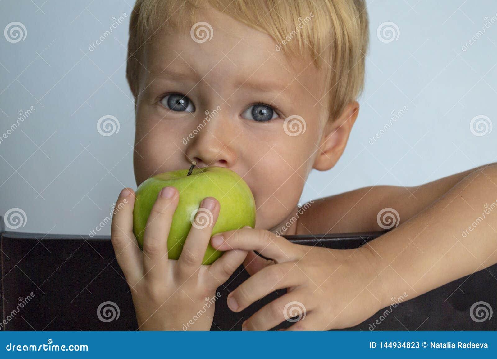 Menino louro europeu bonito que come Apple verde Alimento saud?vel