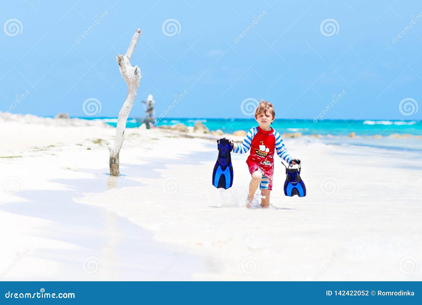 Menino louro pequeno adorável da criança que tem o divertimento na praia tropical de Maldivas Criança entusiasmado que joga e que