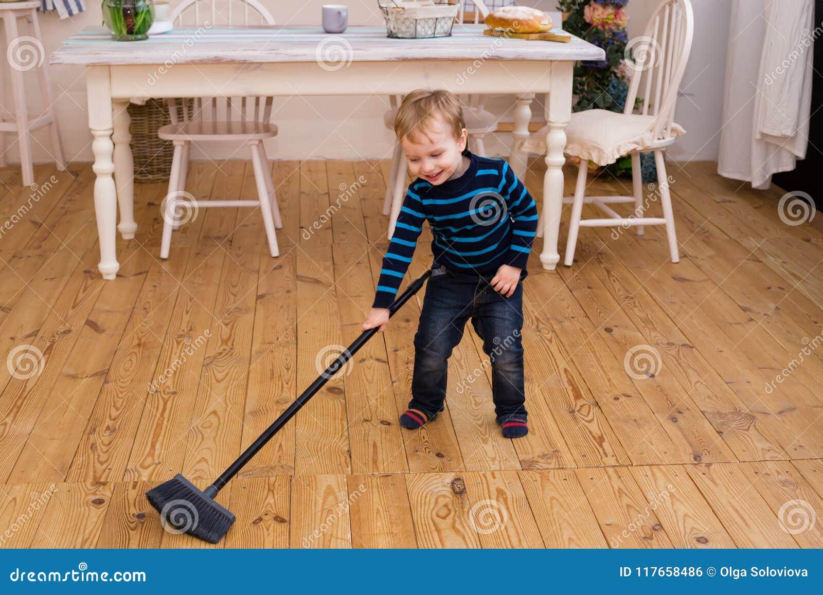 Menino louro pequeno que varre o assoalho na cozinha As ajudas velhas dos yers bonitos do menino 3 parents com trabalhos doméstic