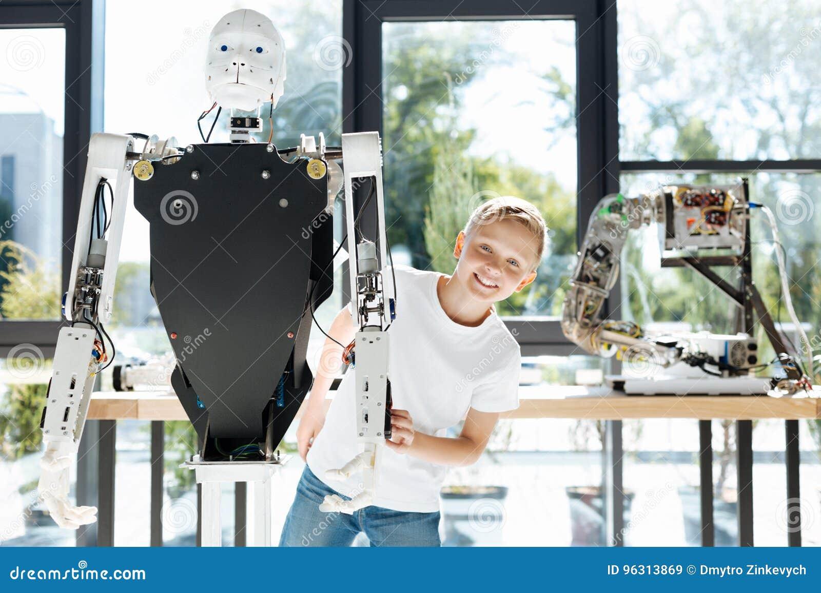Menino louro que emerge atrás de um robô humano