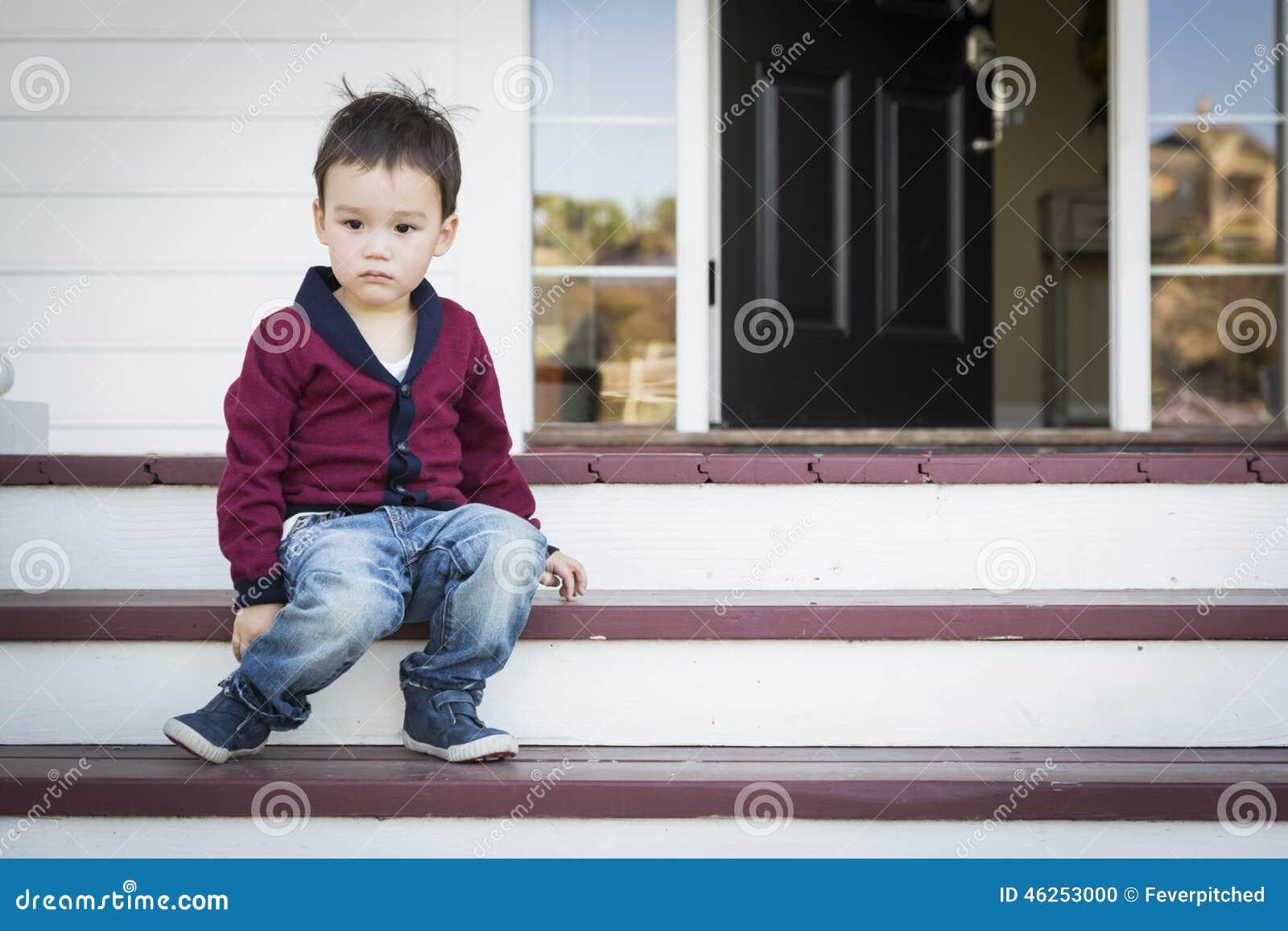 Menino melancólico da raça misturada que senta-se em Front Porch Steps