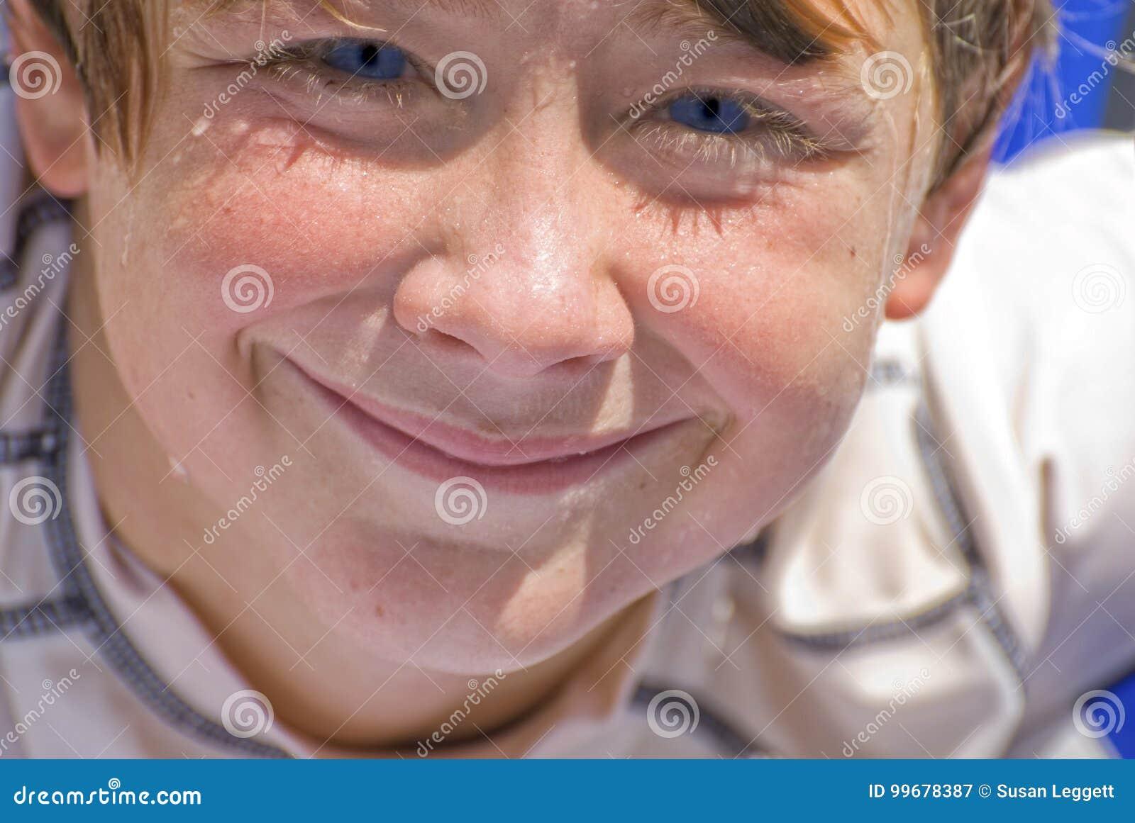Menino molhado de sorriso da cara