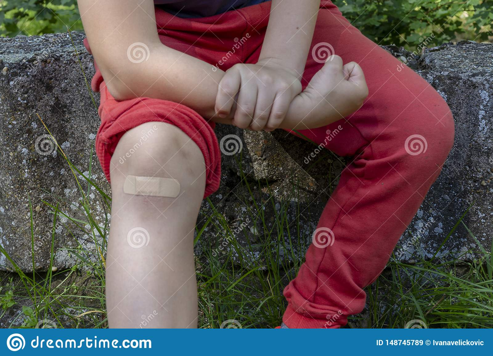 Menino na dor com a atadura em seu joelho