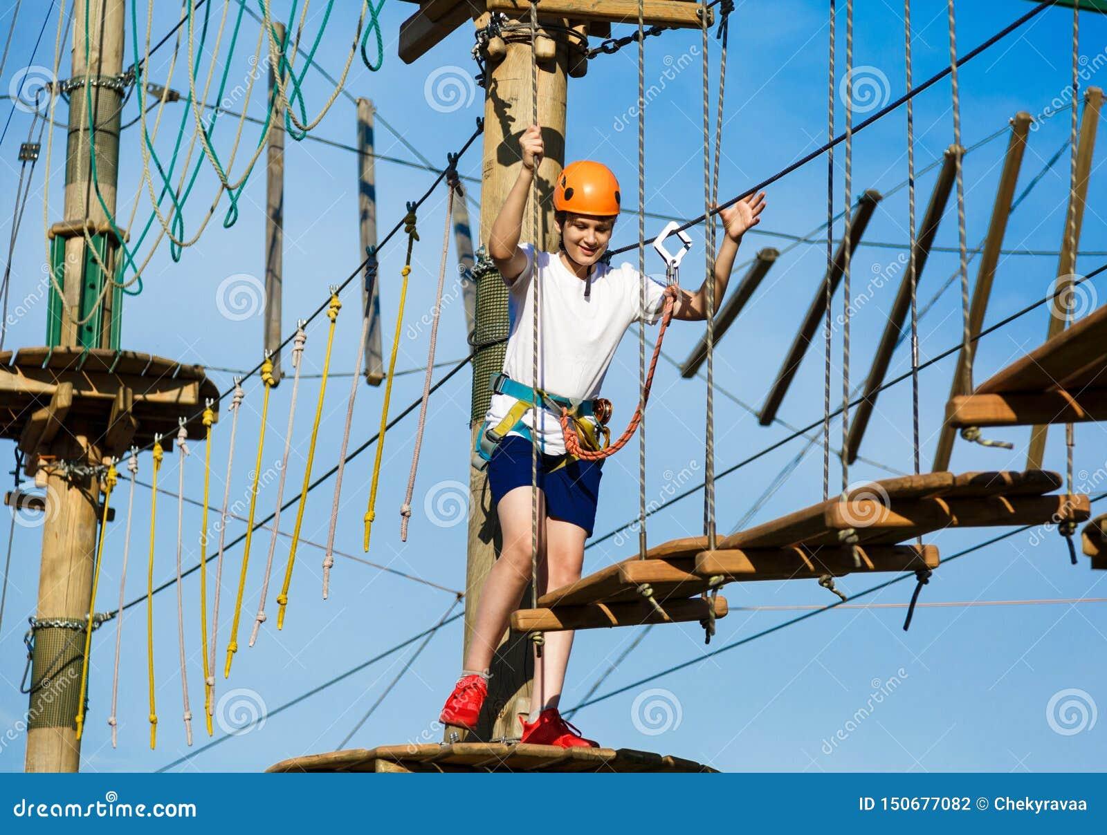 Menino no parque da aventura da floresta A criança no capacete alaranjado e na camisa branca de t escala na fuga alta da corda Es
