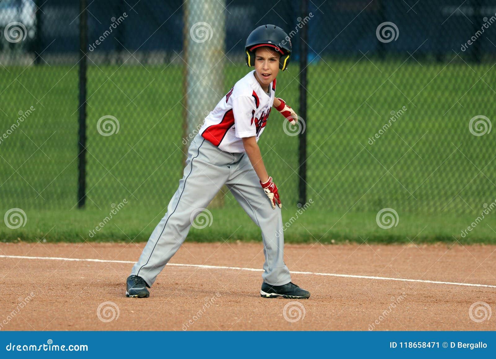 Menino novo bonito considerável que joga o basebol que espera e que protege a base