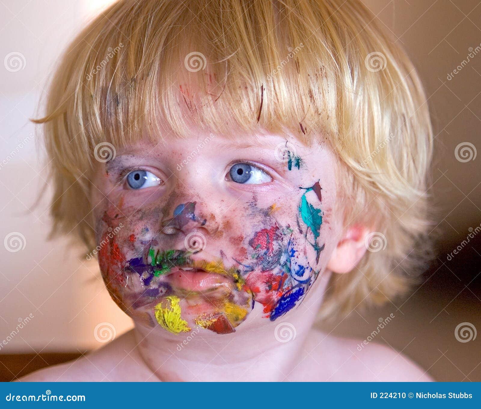 Menino novo coberto na pintura da face