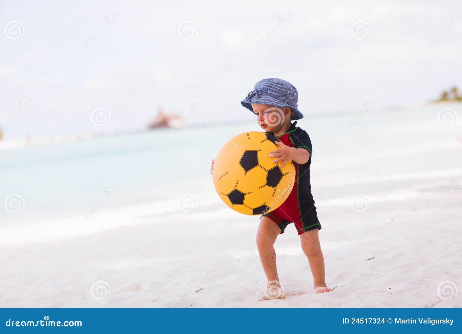 Menino novo com a esfera amarela na praia