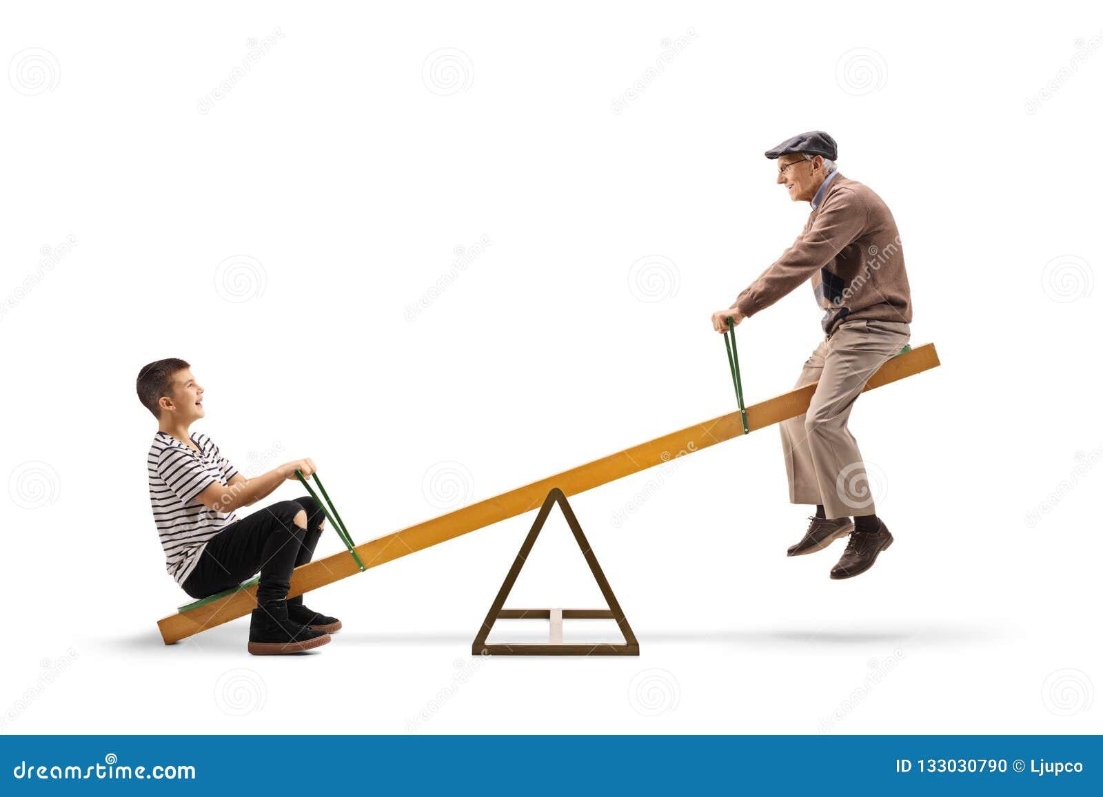 Menino novo e um homem idoso que monta em uma balancê